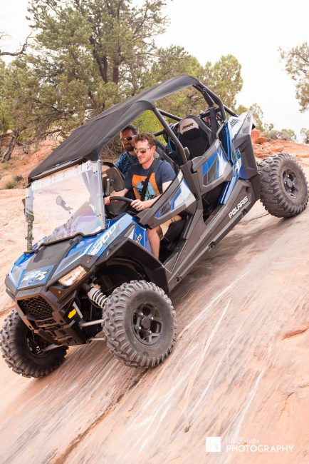 Photograph of a four-wheeler taking a steep downhill rock face of a Moab trail.
