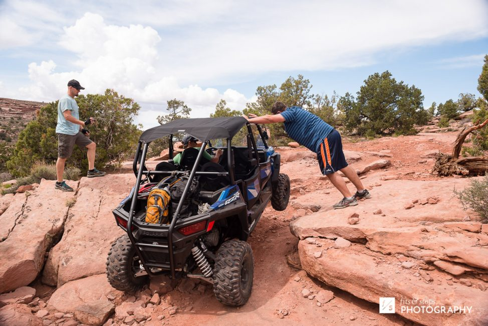 Photograph of a four wheeler working its way up a trail, with one wheel off the ground.