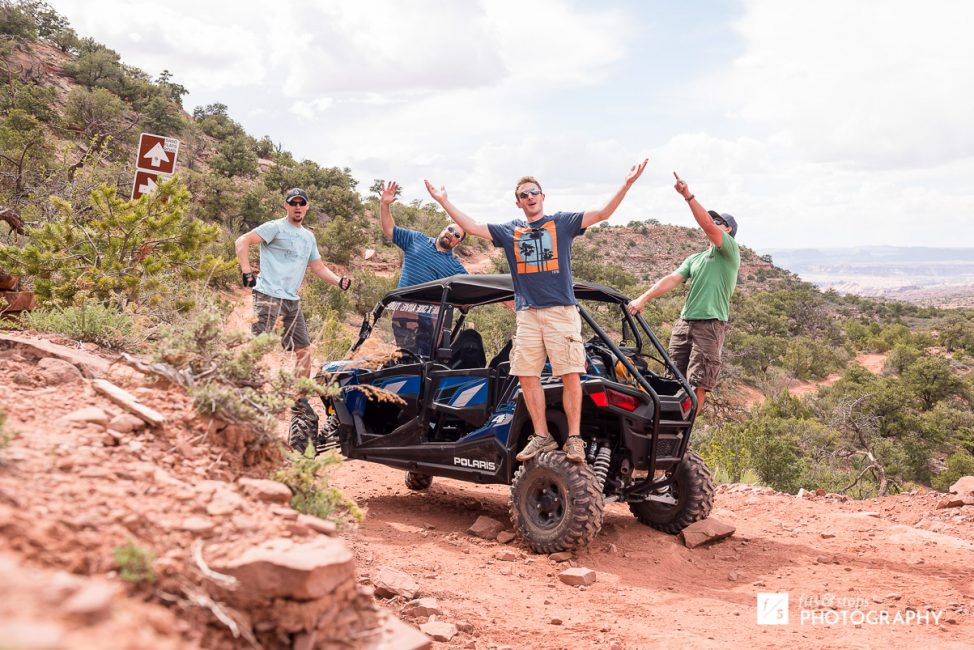 Photograph of four men standing outside their 4WD vehicle on a trail near Moab, Utah.