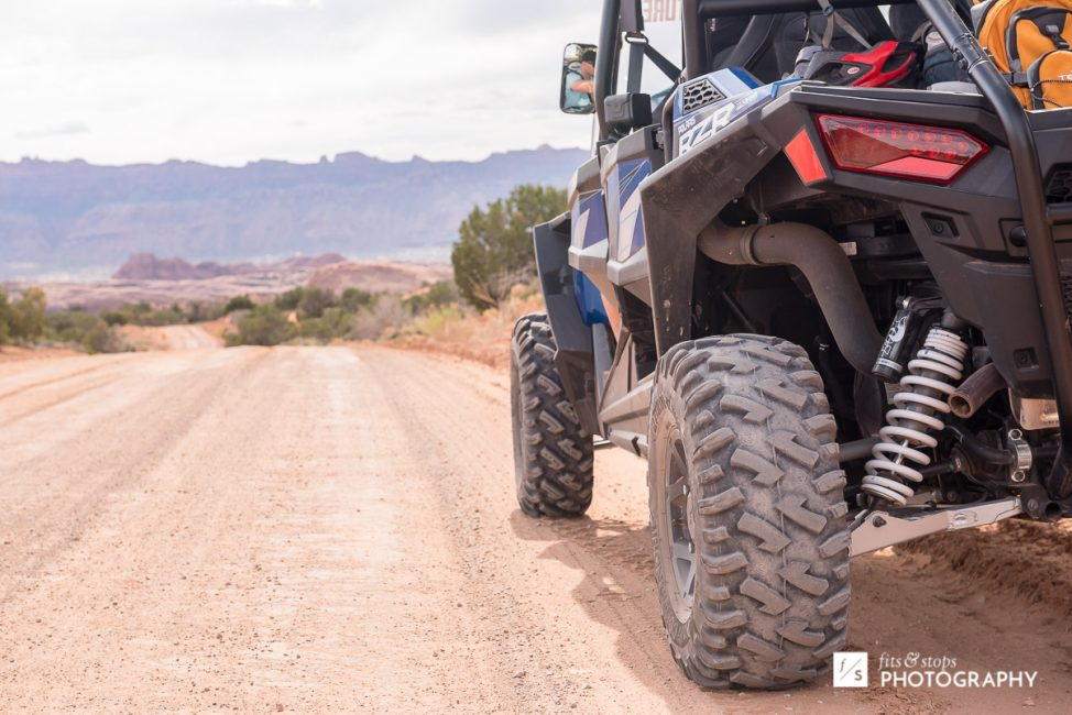 Photograph of the rear end of a Polaris Razor four wheel drive vehicle on a dusty, desert road near Moab, Utah.