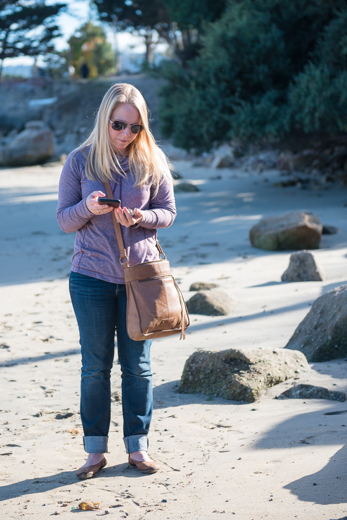 A woman look at her phone while standing on the beach at Fisherman's Shoreline Park.