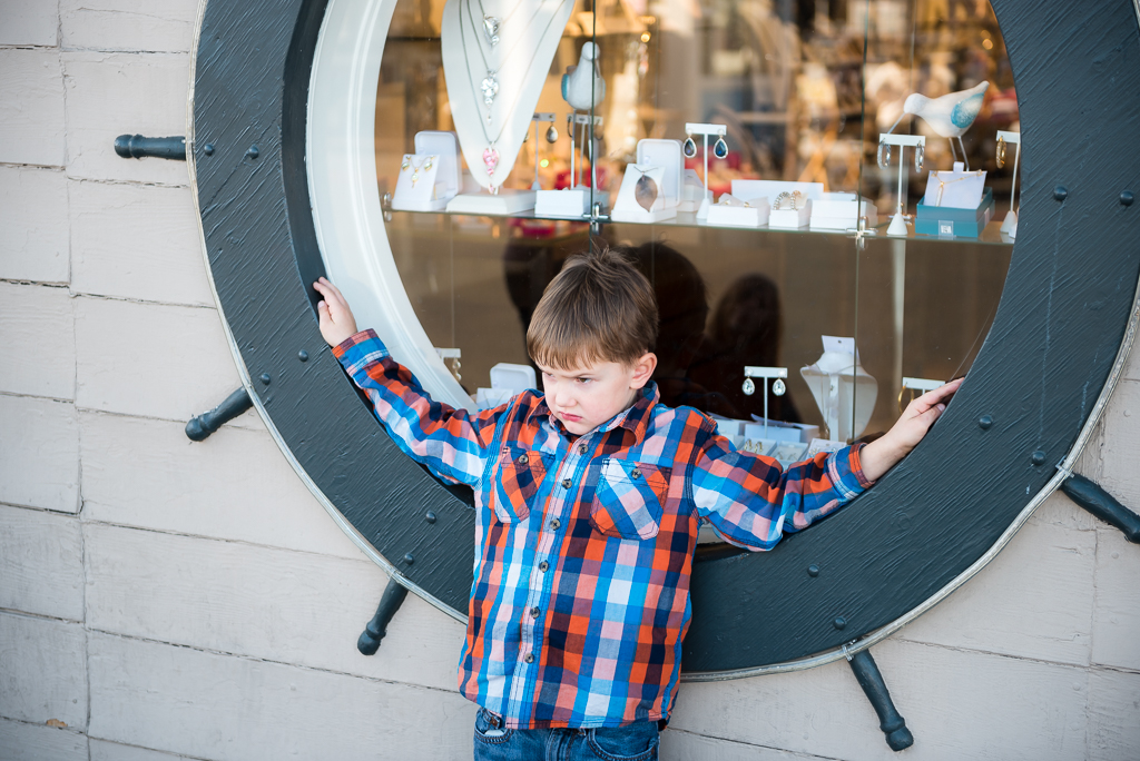 A young boy looks grumpy as he lounges against a window shaped like a ship's steering wheel.