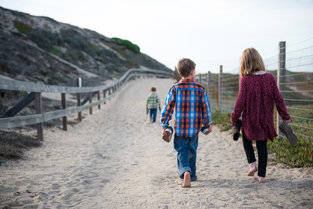 Three young children walk barefoot down a sandy path at Marina State Beach near Seaside, CA.