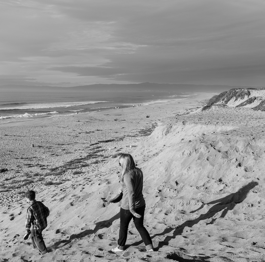 A black and white photograph of a mother and child walking down a sand dune to the beach at Marina State Beach near Seaside, CA.
