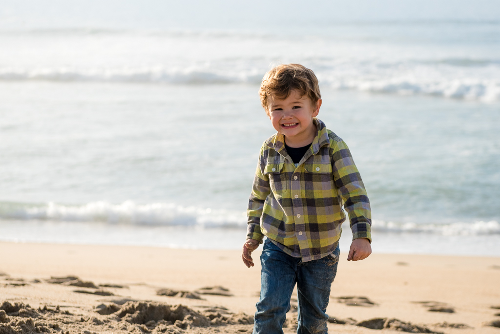 Portrait of a young boy dressed in plaid at the beach.