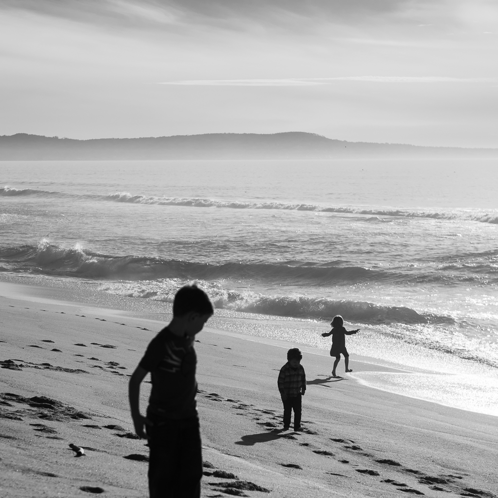 Black and white photograph of three silhouetted children stand in a line leading toward the waves at Marina State Beach.
