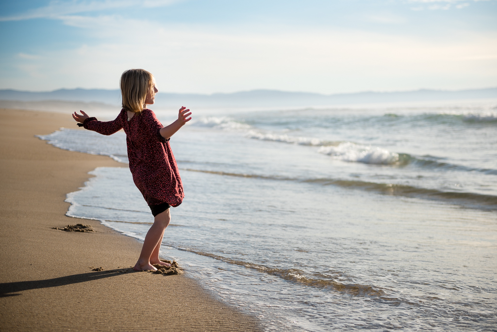 A little girl taunts the ocean waves from the edge of the water.
