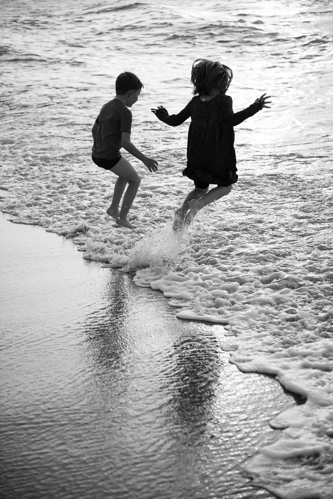 A silhouette of a brother and sister jumping into ocean waves.
