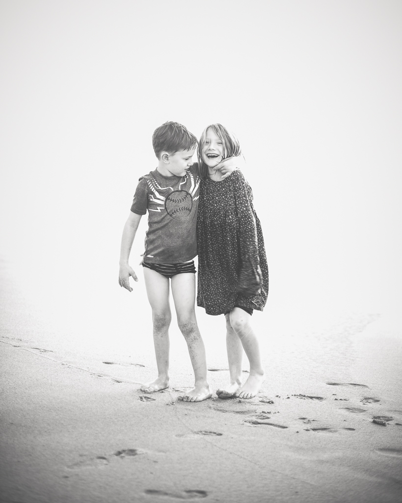 A black and white photo of a brother hugging his big sister on the beach.