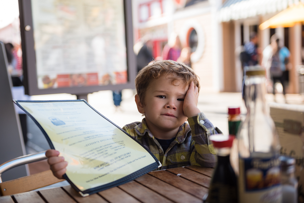 A young boy looks frustrated as he holds a restaurant menu.