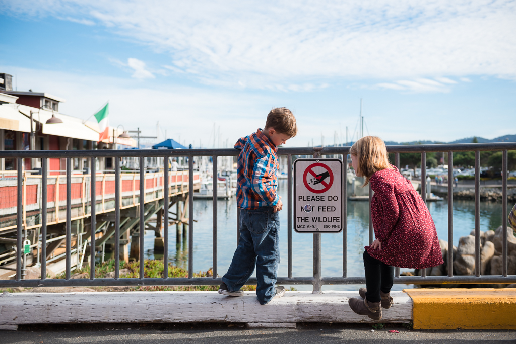 Two children look at a sign that instructs them not to feed the wildlife.