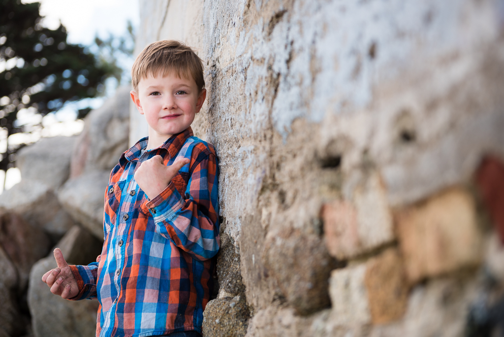 A young boy in a plaid shirt stands against a rock wall in Monterey, CA.