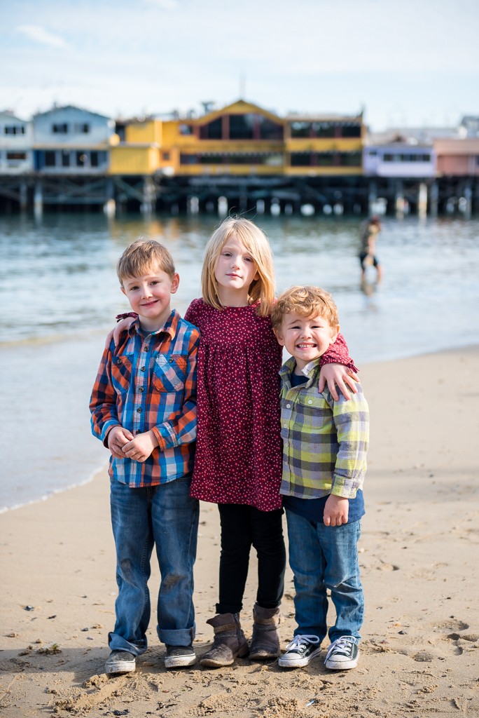 A portrait of three siblings with Fisherman's Wharf in the background at Monterey, CA.