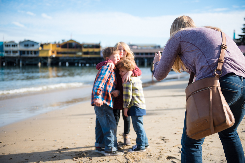 A mom leans over to capture a photo of kids on a beach at Fisherman's Shoreline Park.