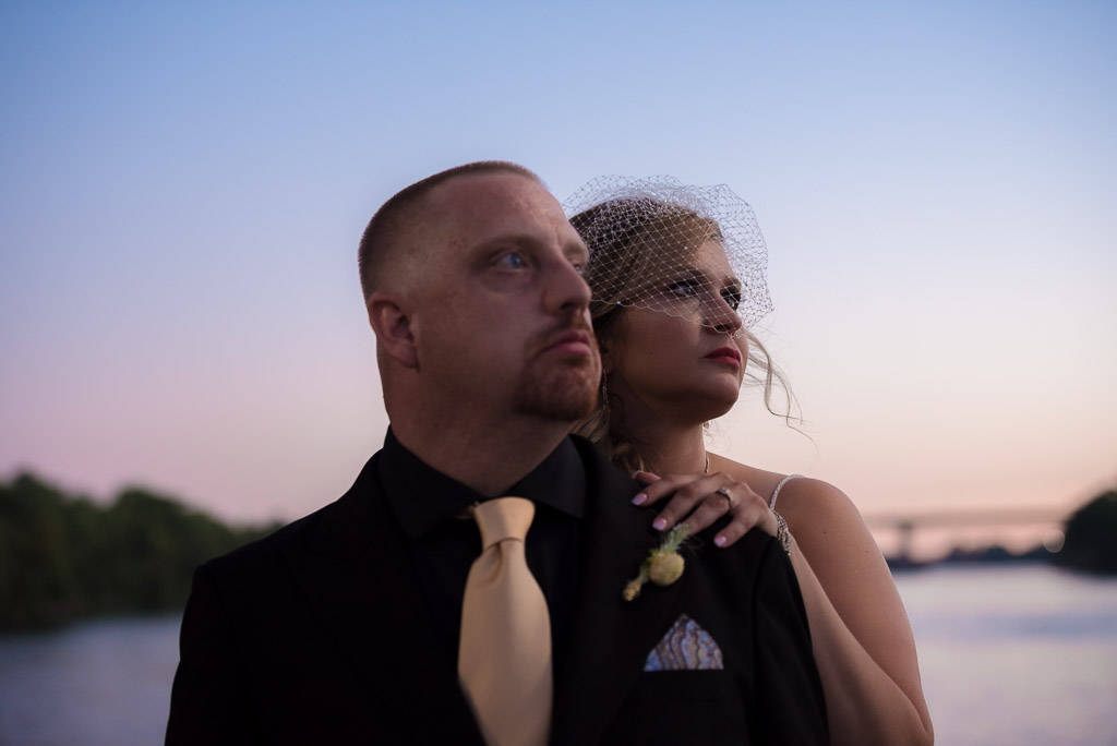 A bride and groom stand in front of the Sacramento river after sunset.