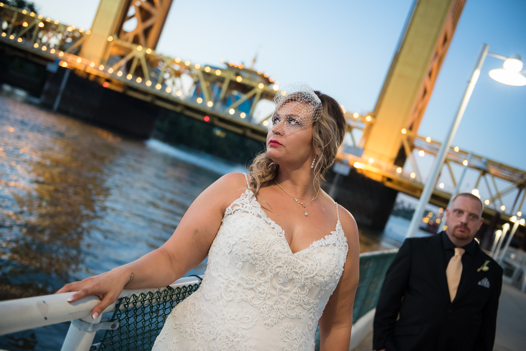 A bride poses with her groom in front of Sacramento's Tower Bridge.