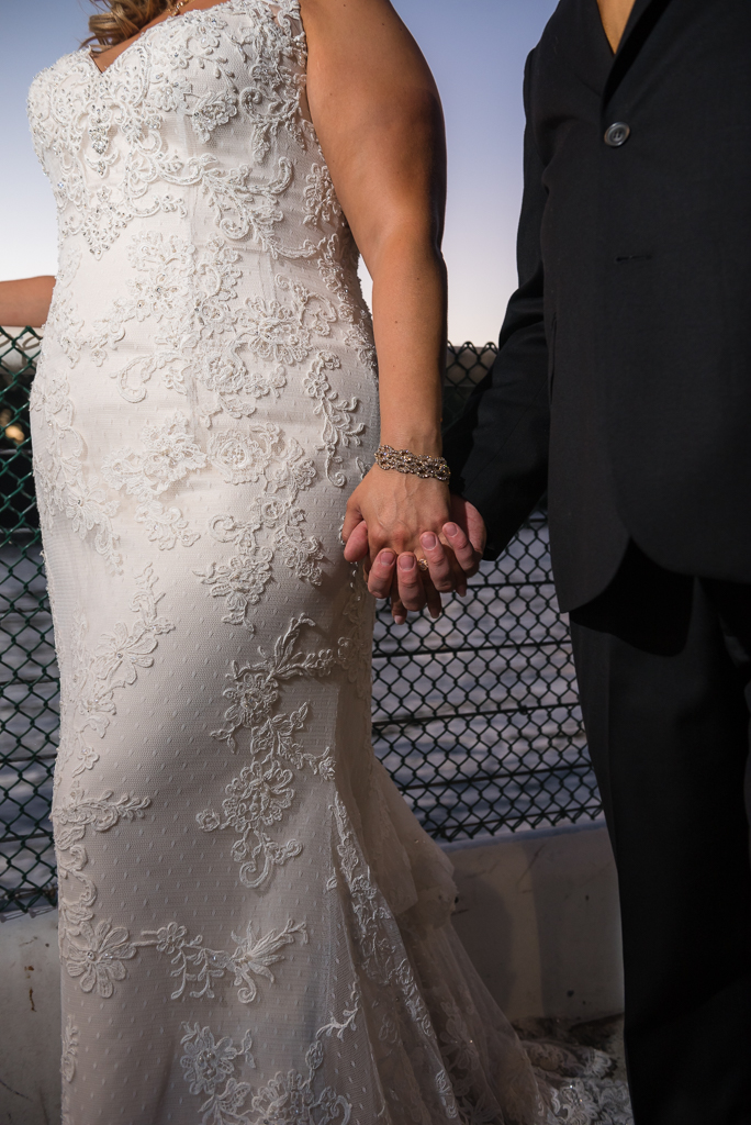 A bride clutches her groom's hand as they stand near the Sacramento River at twilight.