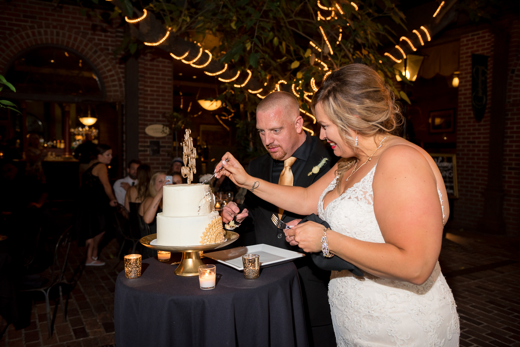 A bride and groom cut their cake at the Firehouse Restaurant Courtyard in Old Sacramento.