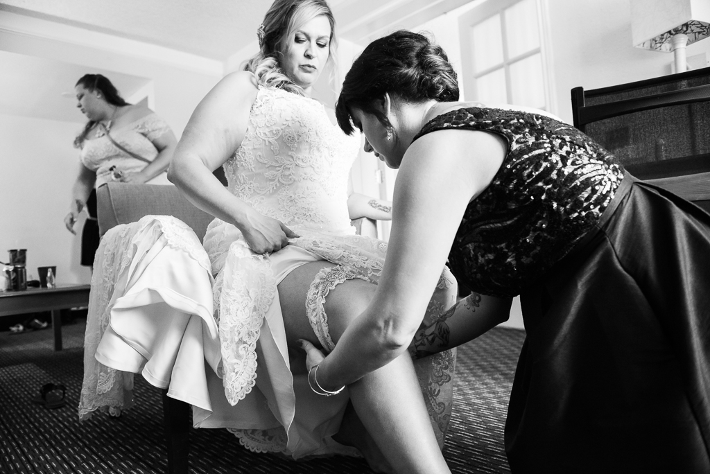 A bridesmaid puts a garter on a bride's leg.