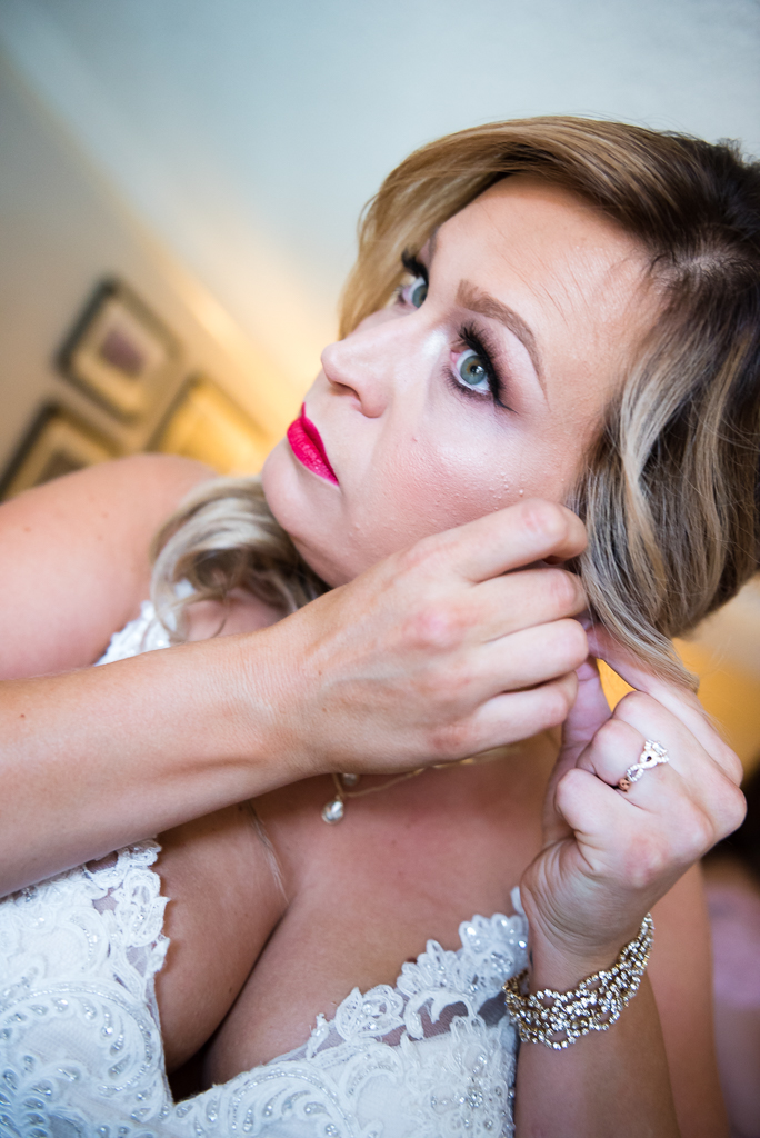 A bride clips on her earring shortly before her Old Sacramento wedding ceremony.