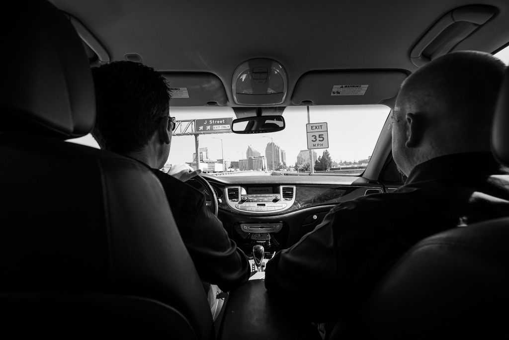 Black and white photo of a groom and groomsman driving toward Old Sacramento.