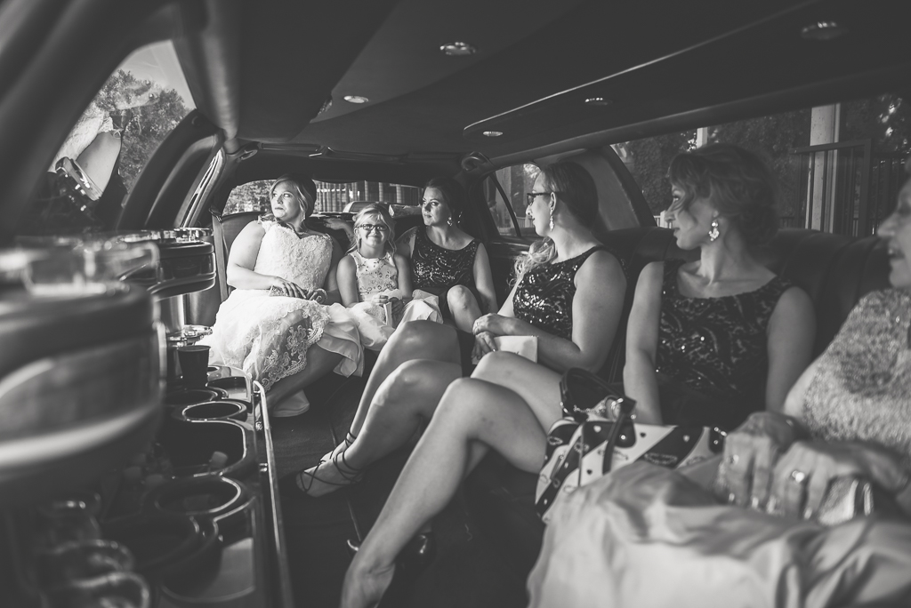 A bride and her bridesmaids ride to Old Sacramento in limo.