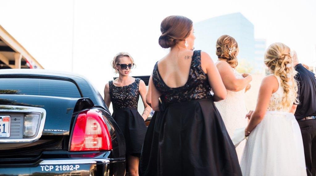 Bridesmaids help a bride exit a limousine.