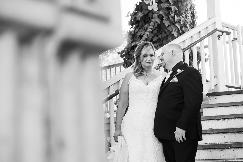 Black and white image of a bride and groom stealing a quick chat on their wedding day.