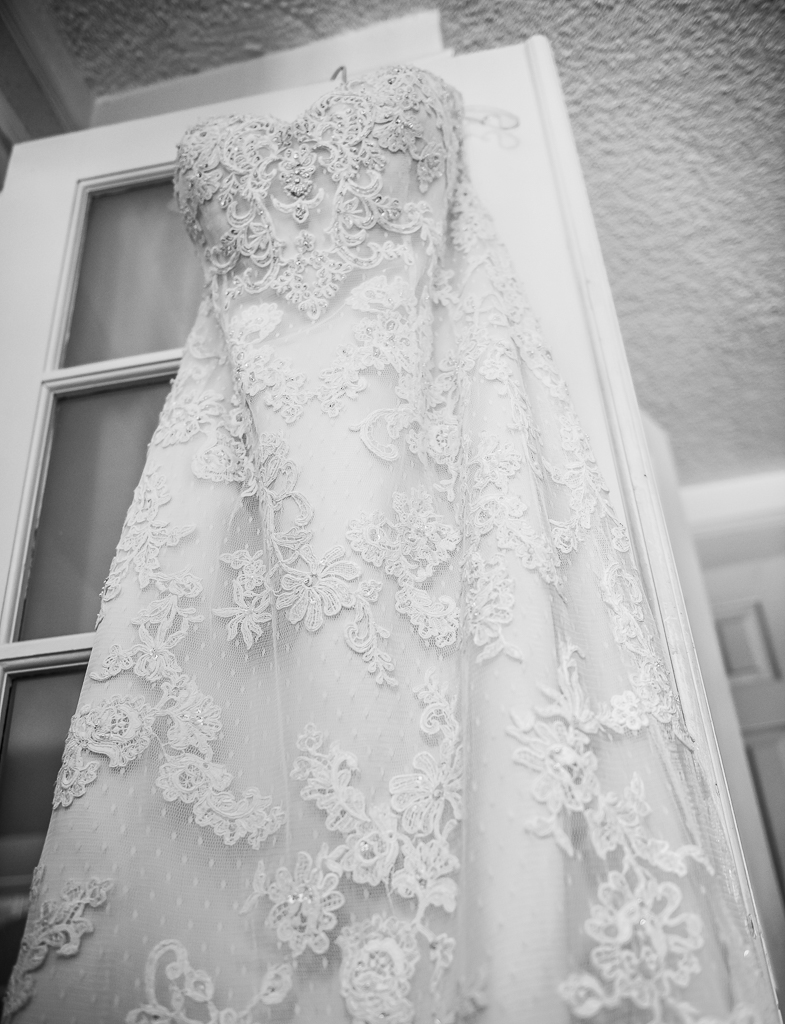 Black and white photo of a wedding dress awaiting its bride.