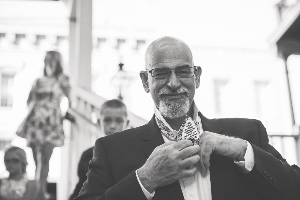 A Father of the bride ties his necktie.