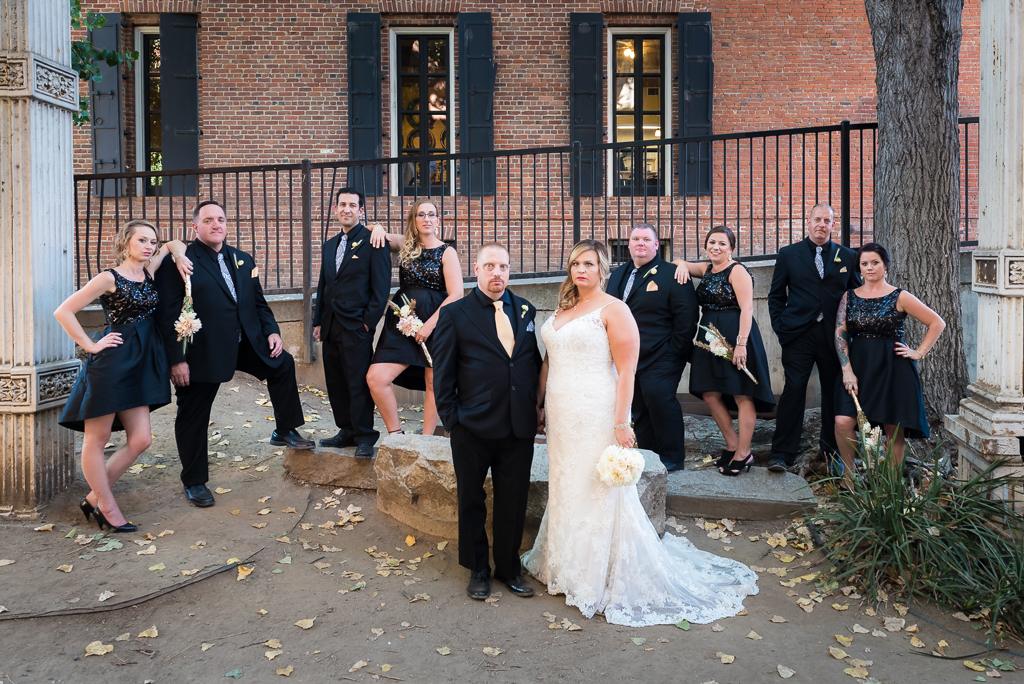 A bridal party poses around the bride and groom at Pioneer Park in Old Sacramento.