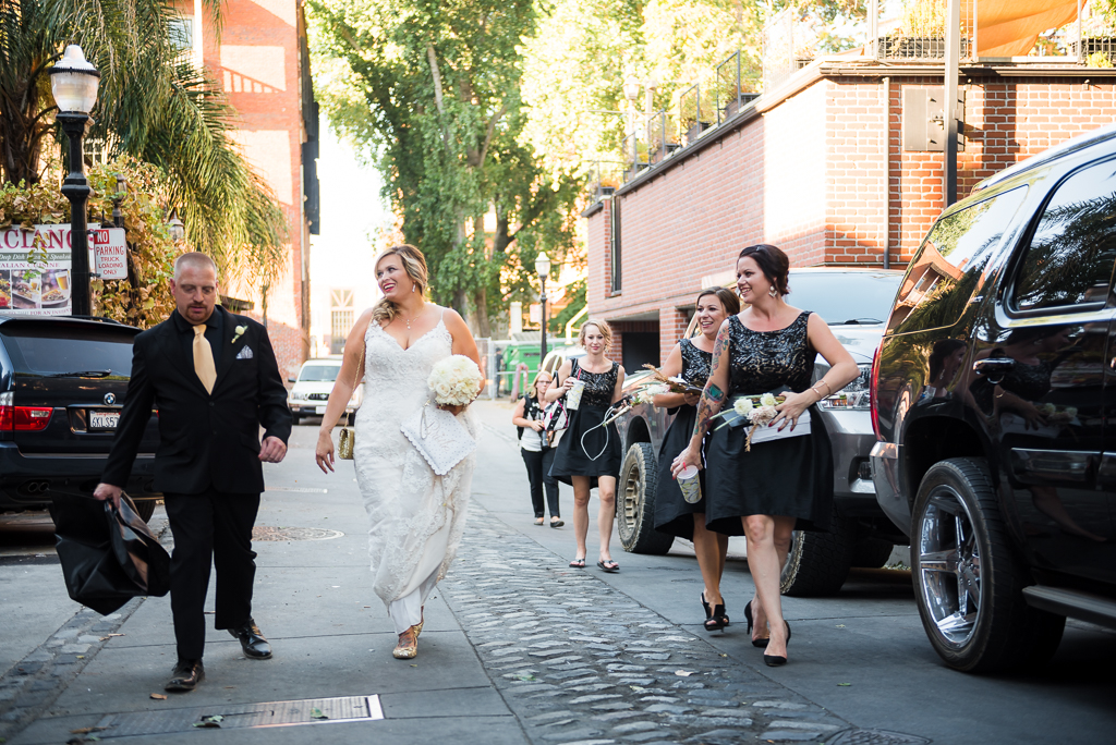A bride, groom and bridal party make their way to the venue.