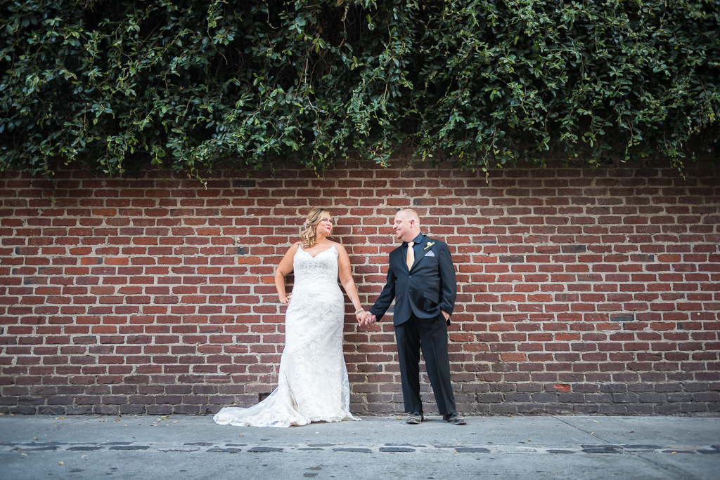 A bride and groom look at eachother underneath a wall of ivy.