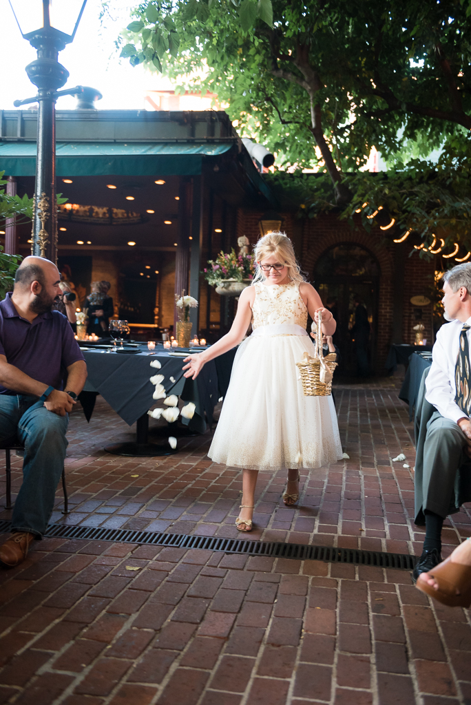 A flower girl tosses petals down the aisle at the FIrehouse Restaurant