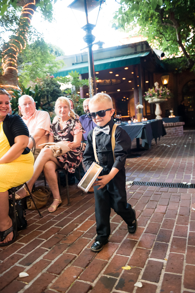 A ring bearer saunters down the aisle at the Firehouse Restaurant