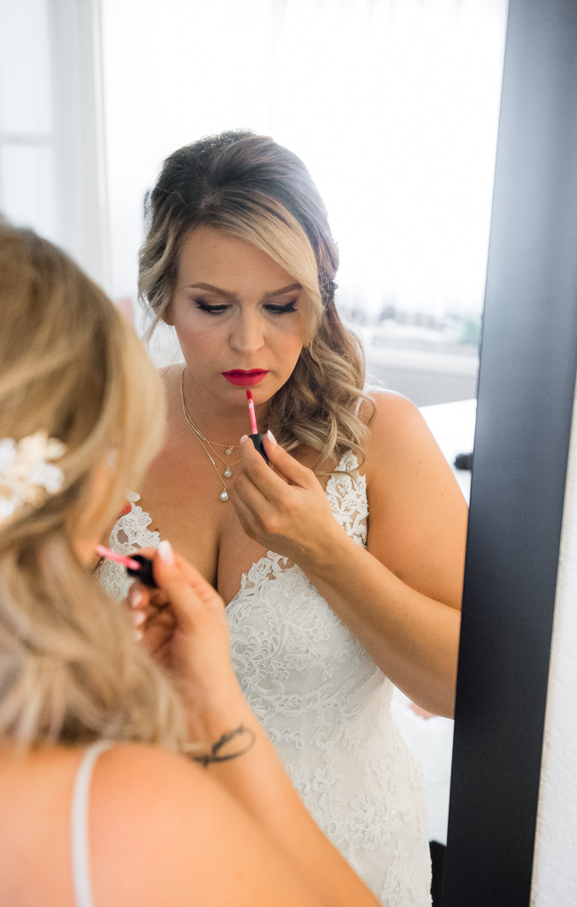 Photograph of a bride applying lip gloss