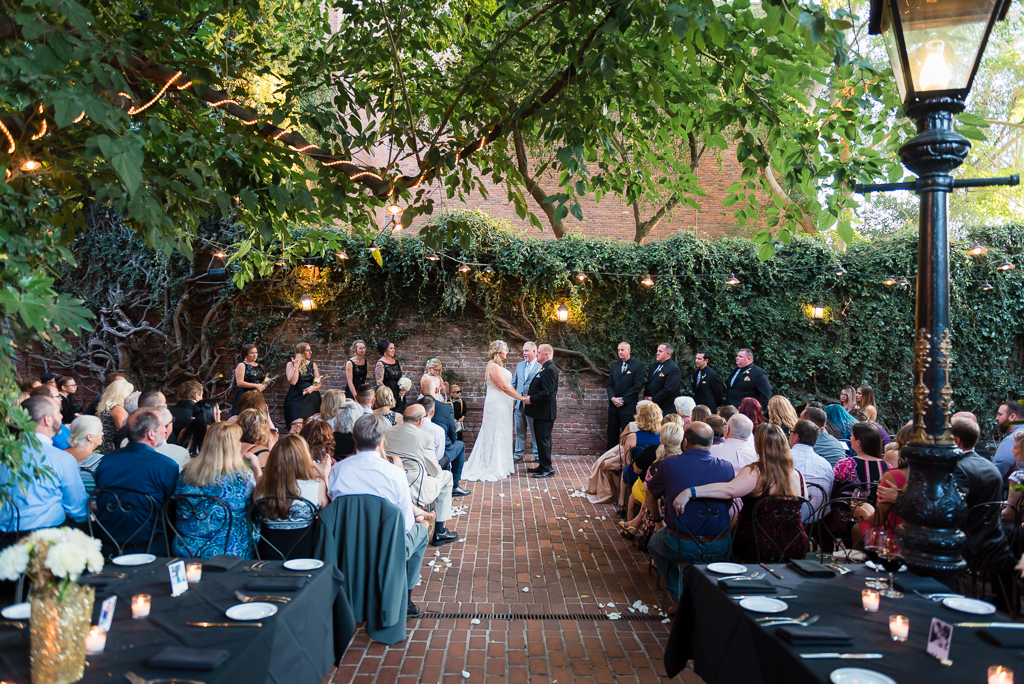 A wide angle view of a wedding at the courtyard at the Firehouse Restaurant.