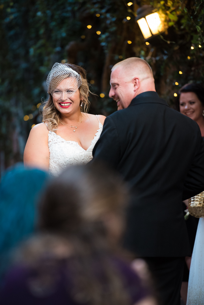 A bride and groom smile widely as they deliver their vows.