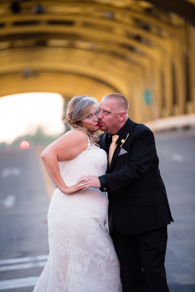 A bride and groom kiss in front of Sacramento's iconic Tower Bridge.