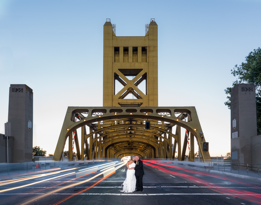 A bride and groom embrace each other in front of Sacramento's Tower Bridge.