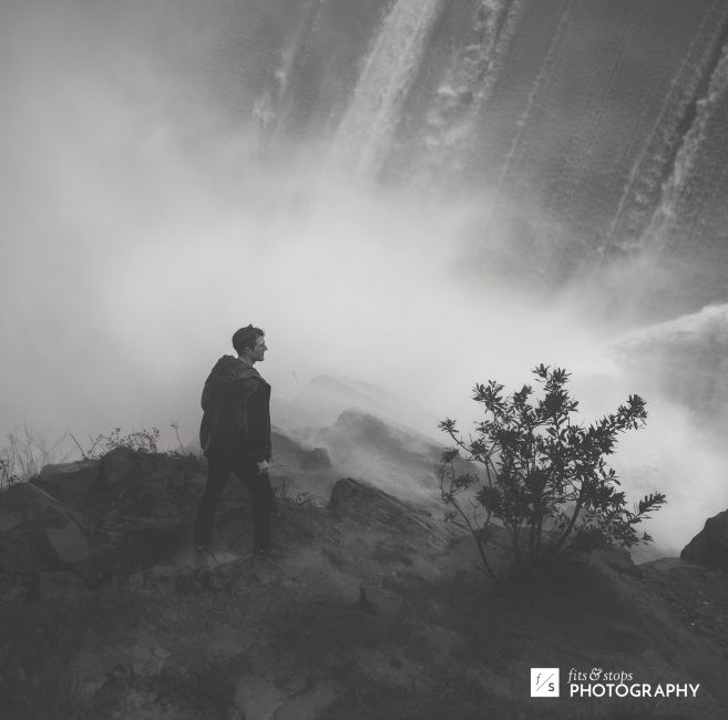 A black and white photograph of a man near the wash of a waterfall.