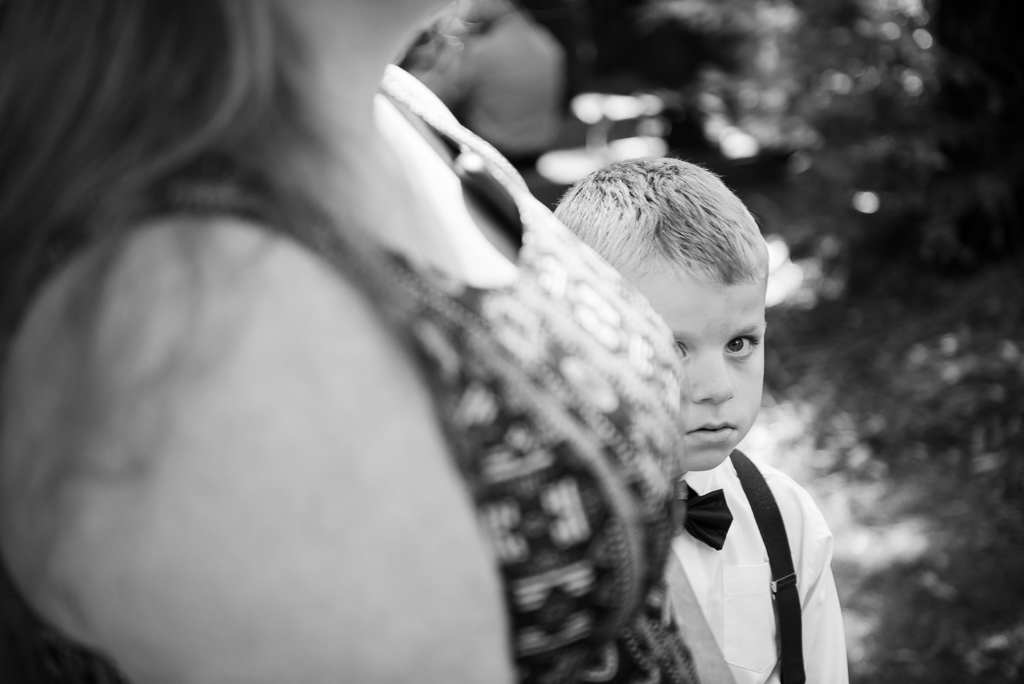 A black and white photo of a boy looking past a woman's chest.