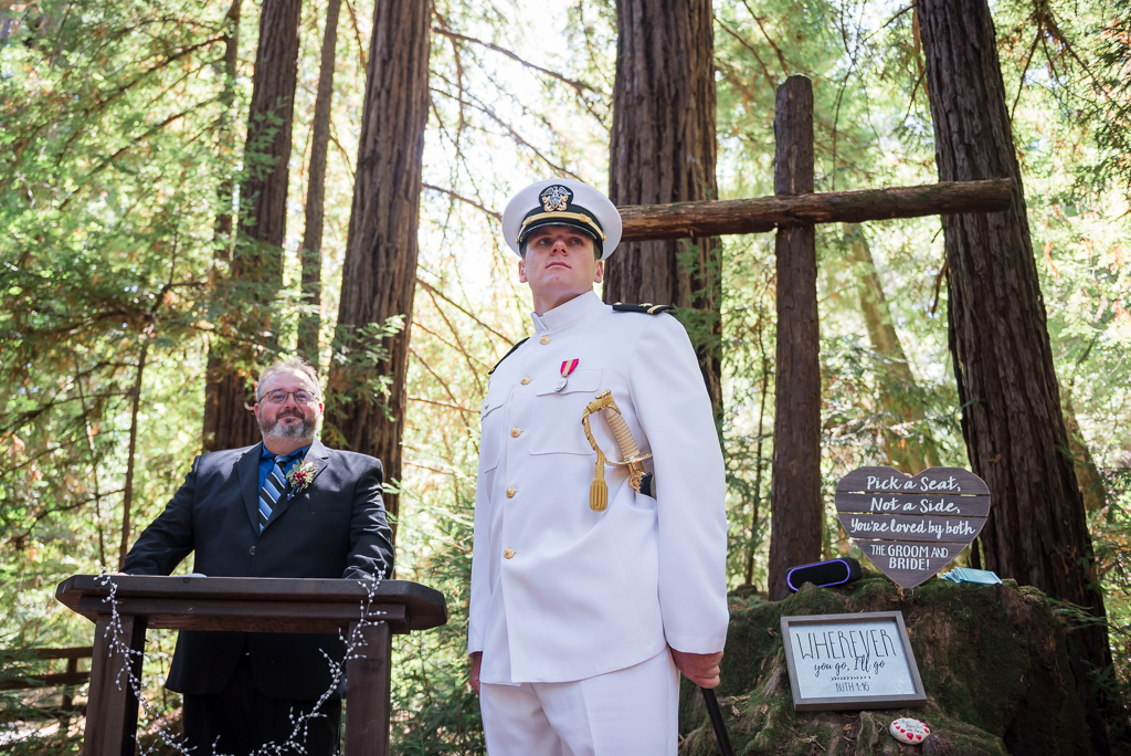 A Navy Officer stands at the end of the aisle in a Redwood forest, waiting to see his bride.