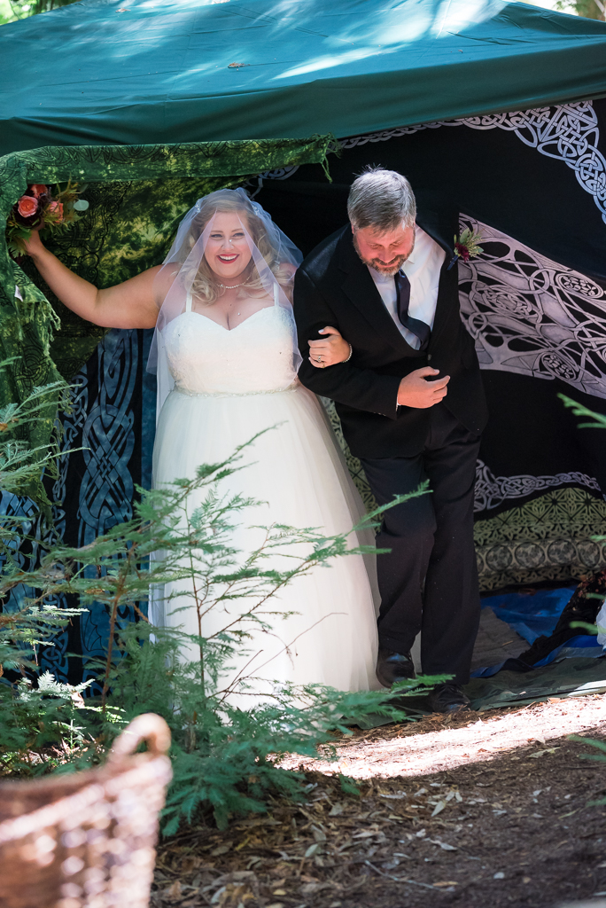 A bride exits her tent in the woods to walk down the aisle with her father.