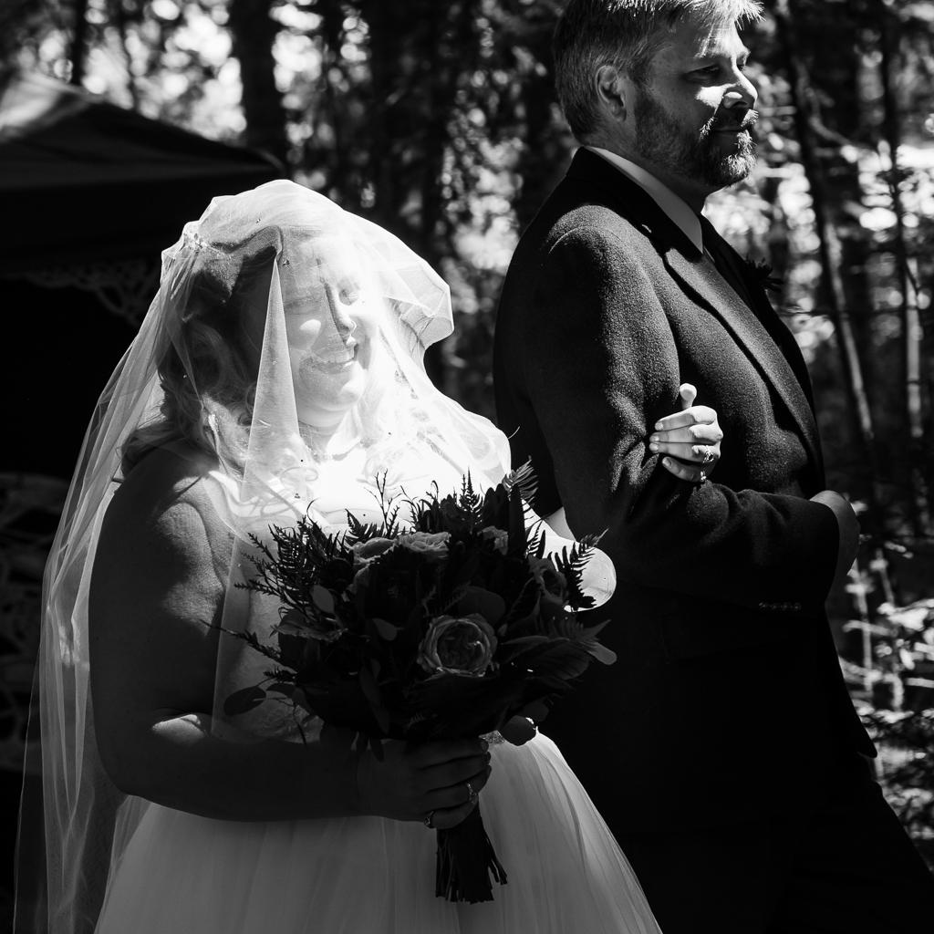 Black and white photo of a father walking his daughter down the aisle at her wedding.