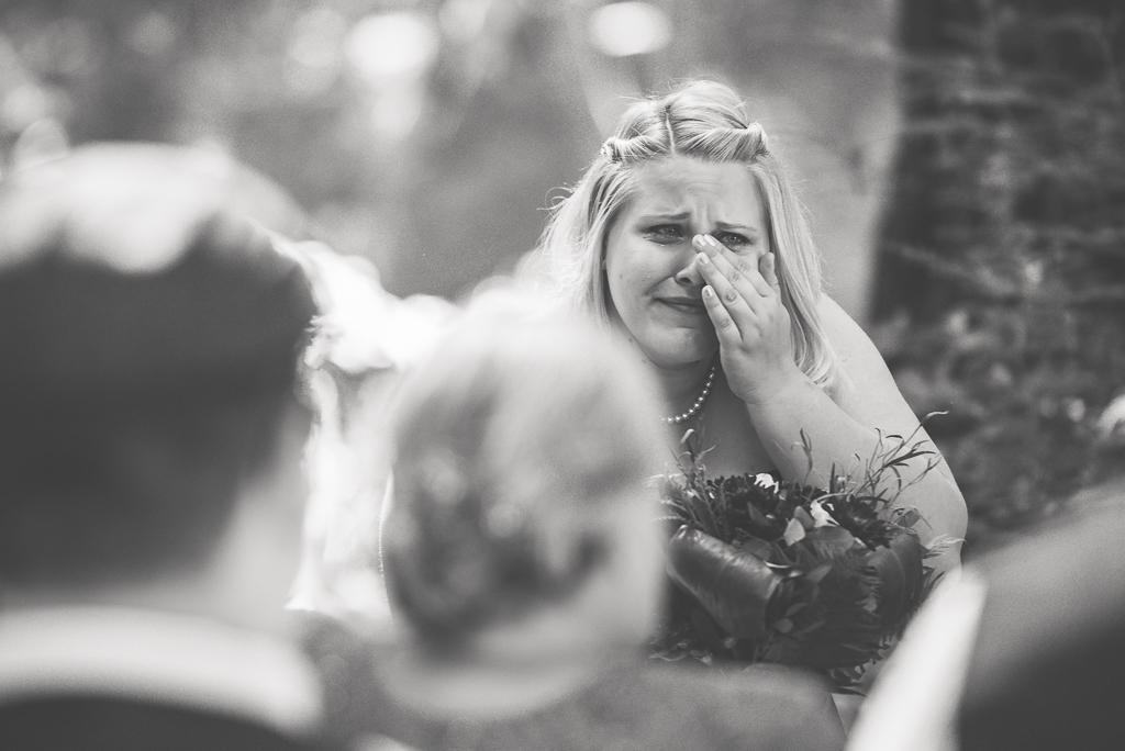 A sister cries as she watches her older sister walk down the wedding aisle.