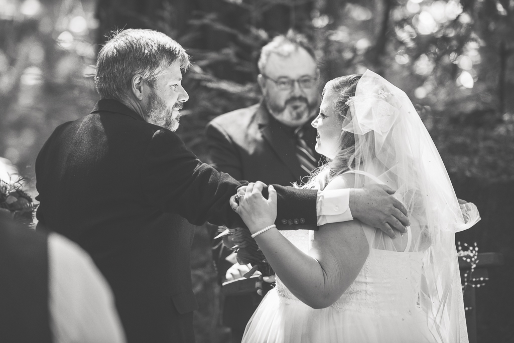 Black and white photo of a father giving away his daughter as a bride.