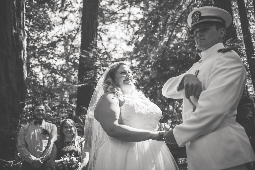 Black and white photo of a groom promising to protect his bride with a sword.