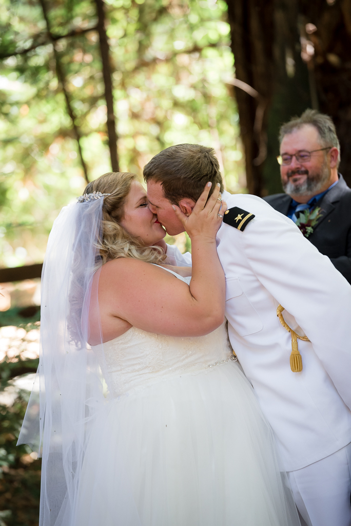 A bride kisses her groom in the redwood grove where they were married.