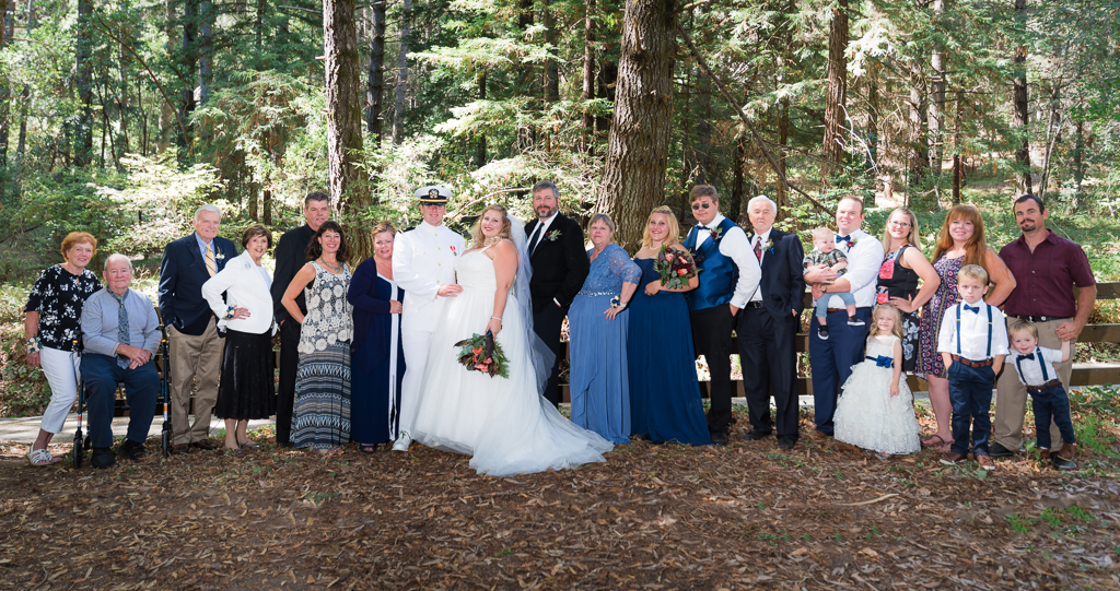 A large family portrait in a wedding a redwood forest.
